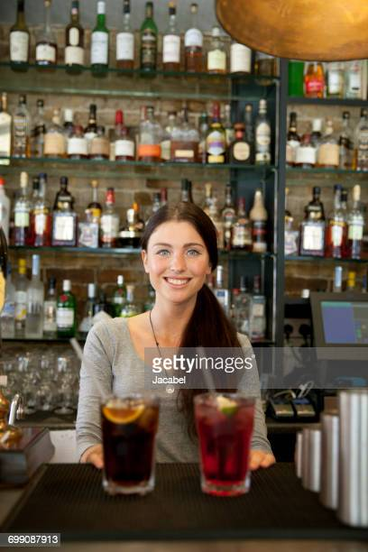 Bartender serving drinks in pub, London