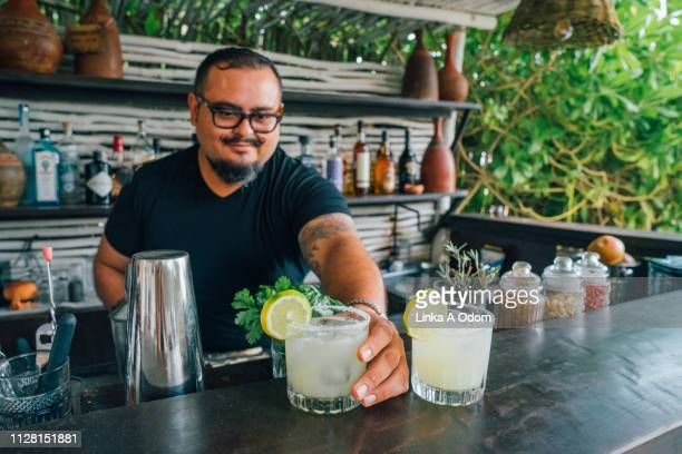 bartender serving margarita's in open air bar - margarita stock pictures, royalty-free photos & images