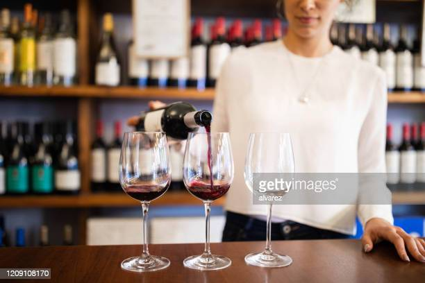 bartender serving red wine in a winery - winery stock pictures, royalty-free photos & images