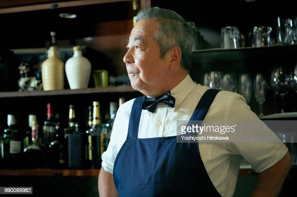 bartender smiling at bar counter - japanese old man stock pictures, royalty-free photos & images