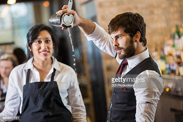 Bartender teaching new employee to make mixed drink behind bar