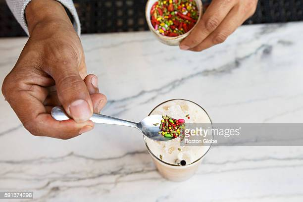 Bartender Tenzin Konchok Samdo sprinkles an Indian fennel seed candy on top of a drink known as Madam Madeline at the restaurant Tavern Road in...