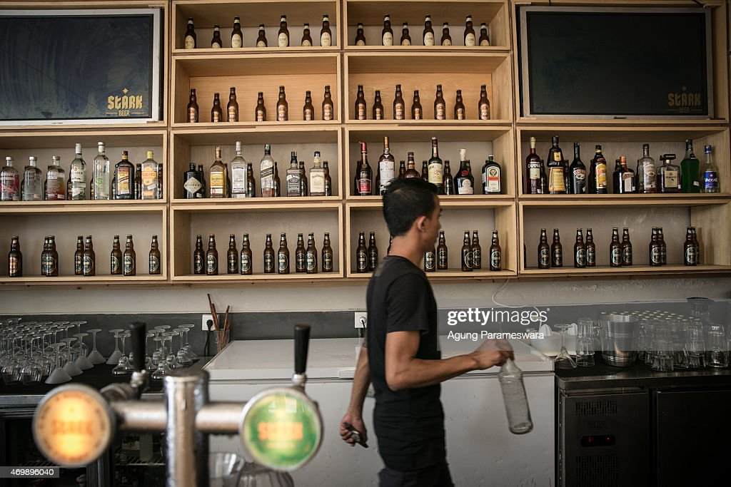 A bartender walks as he prepares a drink in Stark beer house on Legian Street on April 16, 2015 in Kuta, Bali, Indonesia. Indonesia, on April 16, banned small retailers from selling beer which is proposed that legislation by two Islamic parties-the Prosperous Justice Party and the United Development Party-that would ban all consumption of alcoholic drinks and bring jail terms of up to two years for offenders in Indonesia, home to the world's largest Muslim population. The regulation states that it is needed to protect public morals and culture and to improve the control and supervision of alcohol production, distribution and sales. There had been particular anxiety about how the ban might affect tourism on the Hindu-majority resort island of Bali. However, Indonesian trade minister Rachmat Gobel, who was shouted at during an ill-tempered meeting with community leaders in Bali last weekend, has now pledged to ease the restrictions on the island to ensure street vendors can still sell beer at the beach.