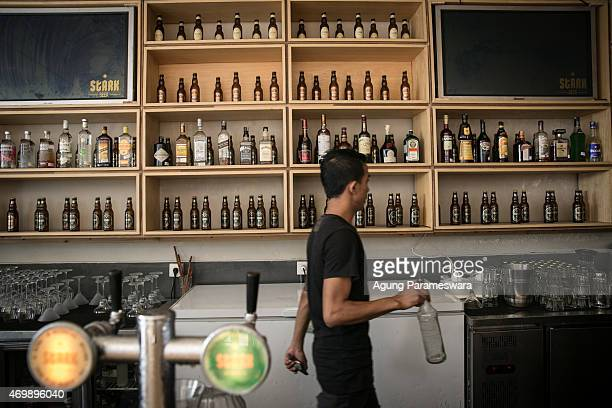 A bartender walks as he prepares a drink in Stark beer house on Legian Street on April 16 2015 in Kuta Bali Indonesia Indonesia on April 16 banned...
