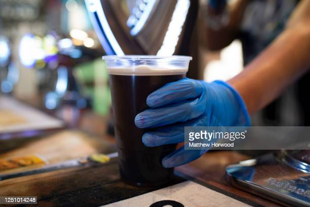 Bartender wearing a blue surgical glove places a pint of Guinness on the bar at the Traders Tavern on June 20, 2020 in Cardiff, United Kingdom. The...