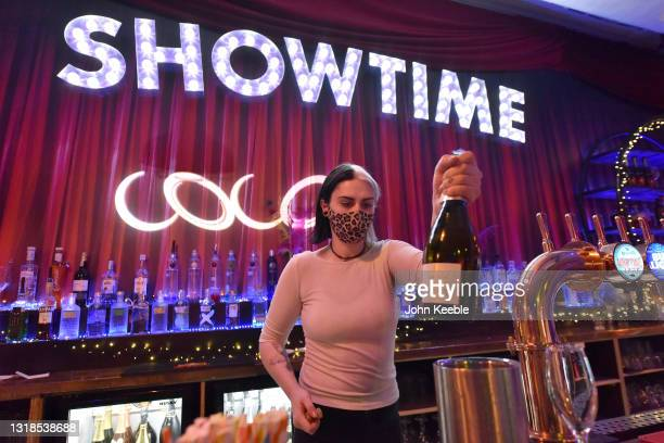 Bartender wearing a face mask prepares a bottle of prosecco at the post lockdown party at Coco bar on May 17, 2021 in Southend, England. From today,...