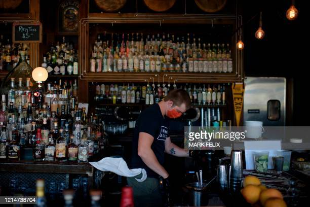 A bartender wearing a facemask and gloves makes drinks at Eight Row Flint in Houston Texas on May 22 amid the novel coronavirus pandemic