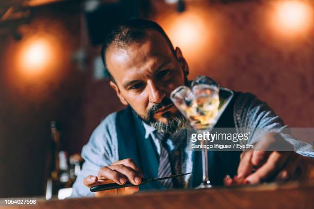 bartender with drink on table at bar - bartender stock pictures, royalty-free photos & images