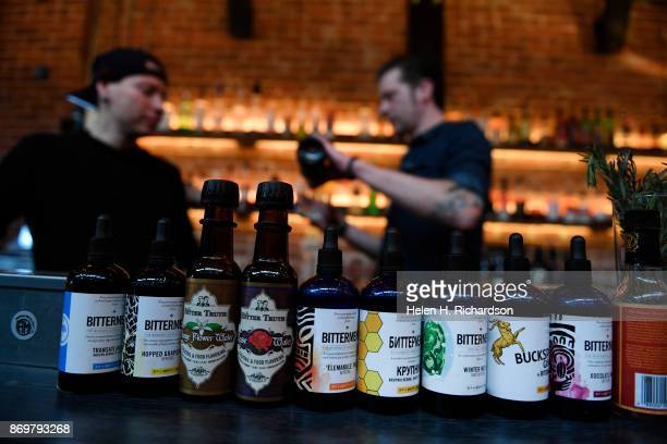 DENVER CO OCTOBER 24 Bartenders Charlie Long left and J Jenson right tend the bar at the new bar called SneekEazy with a row of a variety of bitters...