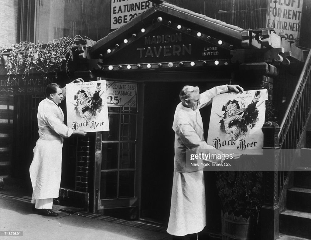 Bartenders putting up advertisements for Bock beer outside the Madison Tavern after the end of prohibition, New York, 5th March 1934.