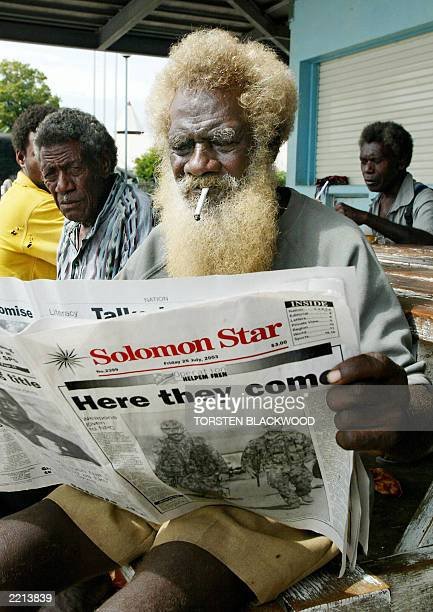 Bartley Beuko catches up on the news at the fish markets in Honiara 25 July 2003 that the first 800 soldiers from the Australianled intervention...