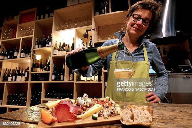 barTO Wine specialist Lucile Mourot fills a glass of champagne to be served with cheese and ham at the bar 'Aux 3 p'tits bouchons' in Reims...