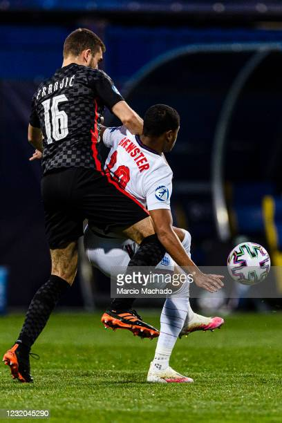 Bartol Franjic of Croatia battles for the ball with Rhian Brewster of England during the 2021 UEFA European Under-21 Championship Group D match...