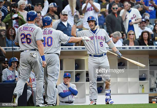 Bartolo Colon of the New York Mets, center, is congratulated by David Wright as Kevin Plawecki looks on after Colon hit a two-run home run for the...