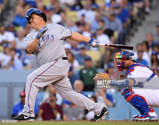 Bartolo Colon of the Texas Rangers loses his helmet as he grounds out to end the first inning in front of Yasmani Grandal of the Los Angeles Dodgers...