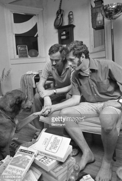 K Barton Osborn and Michael Uhl two former US military intelligence agents play with Uhl's dog Siegfried at their home Earlier appearing before House...