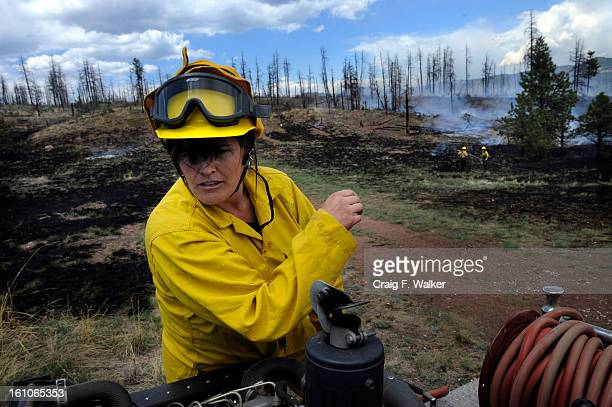 barton_060308_CFW LT Alisha Alitz of the Mountain Community Volunteer Fire Department works to contain a grass fire in the Hayman burn area off...