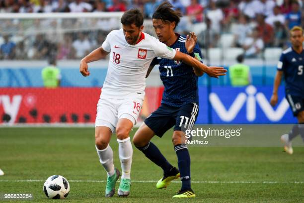 Bartosz Bereszynski of Poland and Takashi Usami of Japan during the 2018 FIFA World Cup Group H match between Japan and Poland at Volgograd Arena in...