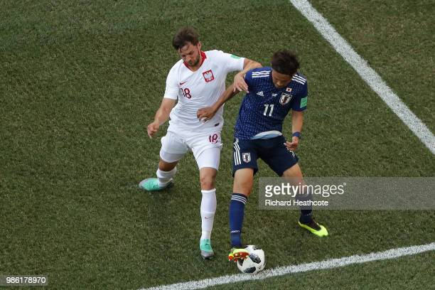 Bartosz Bereszynski of Poland tackles Takashi Usami of Japan during the 2018 FIFA World Cup Russia group H match between Japan and Poland at...
