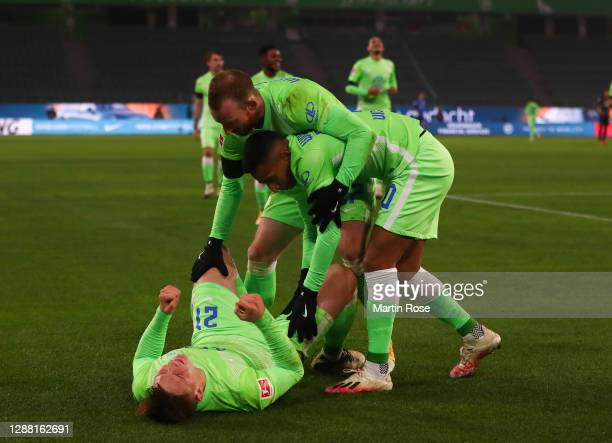 Bartosz Bialek celebrates scoring the fifth goal with Maximilian Arnold and Jérôme Roussillon of Wolfsburg during the Bundesliga match between VfL...