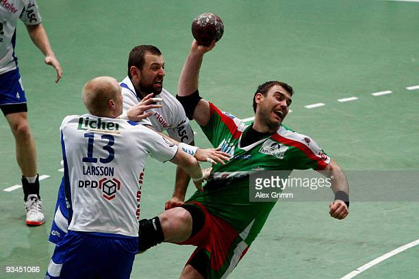 Bartosz Jurecki of Magdeburg is challenged by Sverre Jakobsson and Joakim Larsson of Grosswallstadt during the Toyota Handball Bundesliga match...