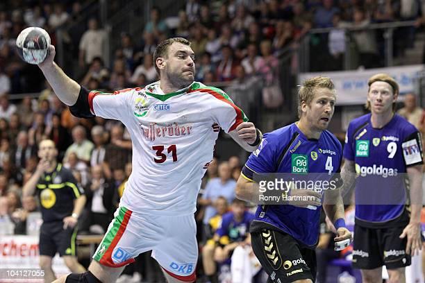 Bartosz Jurecki of Magdeburg scores against Oliver Roggisch and Borge Lund of Rhein Neckar Loewen during the Toyota Handball Bundesliga match between...