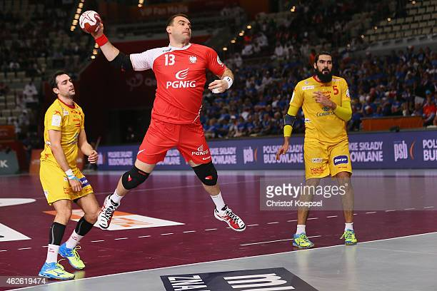 Bartosz Jurecki of Poland scores a goal againstagainst Julen Aguinagalde of Spain and Jorge Maqueda of Spain during the third place match between...