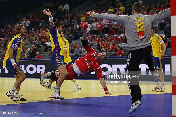 Bartosz Jurecki of Poland scores a goal Andreas Palicka of Sweden and Kim Andersson of Sweden during the Men's European Handball Championship second...