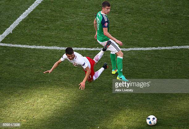 Bartosz Kapustka of Poland and Paddy McNair of Northern Ireland compete for the ball during the UEFA EURO 2016 Group C match between Poland and...
