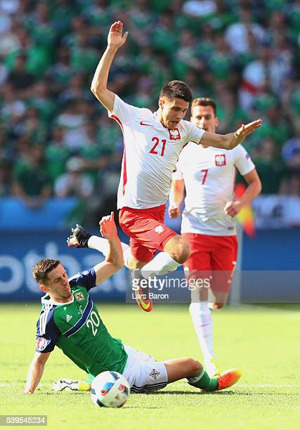 Bartosz Kapustka of Poland is tackled by Craig Cathcart of Northern Ireland during the UEFA EURO 2016 Group C match between Poland and Northern...