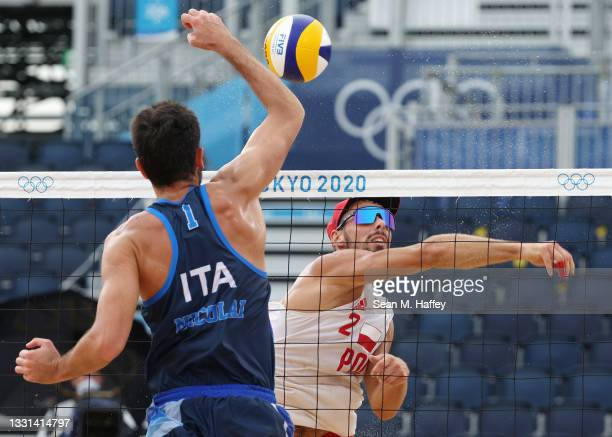 Bartosz Losiak of Team Poland competes against Paolo Nicolai of Team Italy during the Men's Preliminary - Pool F beach volleyball on day seven of the...
