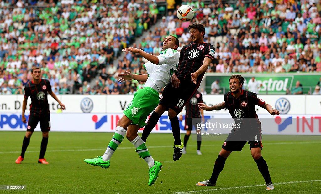 Bas Dost of VfL Wolfsburg goes up for a header with David Abraham of Eintracht Frankfurt during the Bundesliga match between VfL Wolfsburg and Eintracht Frankfurt at Volkswagen Arena on August 16, 2015 in Wolfsburg, Germany.
