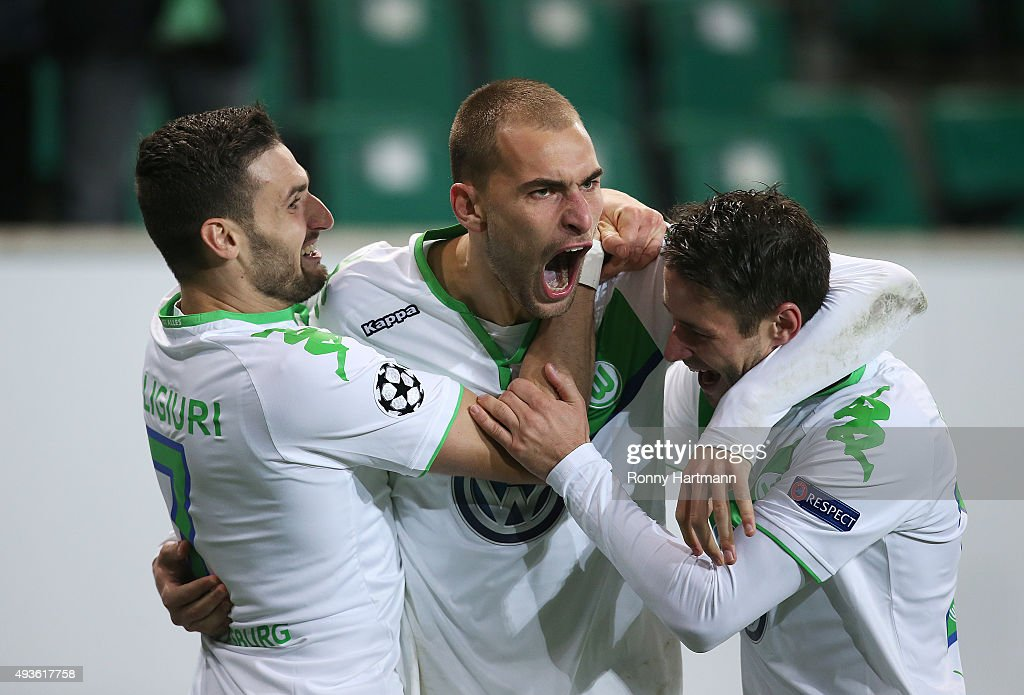 Bas Dost (C) of Wolfsburg celebrates after scoring his team's opening goal with Daniel Caligiuri (L) of Wolfsburg and Christian Traesch (R) of Wolfsburg during the UEFA Champions League Group B match between VfL Wolfsburg and PSV Eindhoven at Volkswagen Arena on October 21, 2015 in Wolfsburg, Germany.