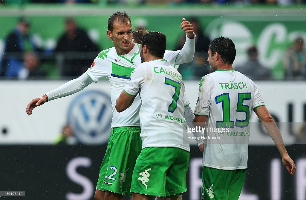 Bas Dost of Wolfsburg celebrates after scoring his team's second goal with Daniel Caligiuri and Christian Traesch of Wolfsburg during the Bundesliga match between VfL Wolfsburg and Hertha BSC at Volkswagen Arena on September 19, 2015 in Wolfsburg, Germany.
