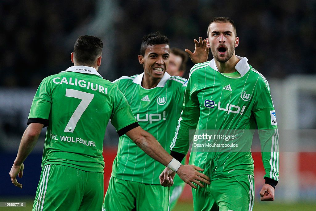 Bas Dost (R) of Wolfsburg celebrates scoring his teams second goal of the game during the Bundesliga match between Borussia Moenchengladbach and VfL Wolfsburg held at Borussia-Park on December 22, 2013 in Moenchengladbach, Germany.