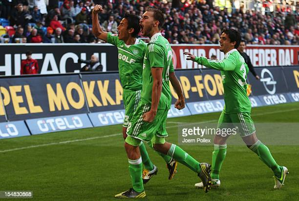 Bas Dost of Wolfsburg celebrates with his team mates Fagner and Makoto Hasebe after scoring his team's third goal during the Bundesliga match between...