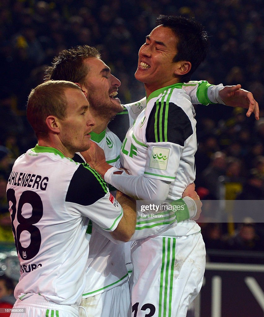 Bas Dost of Wolfsburg celebrates with team mate Makoto Hasebe after scoring his teams third goal during the Bundesliga match between Borussia Dortmund and VfL Wolfsburg at Signal Iduna Park on December 8, 2012 in Dortmund, Germany.