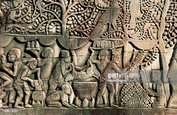Bas relief at the Bayon temple in Angkor. This scene depicts a group of people organising a meal..