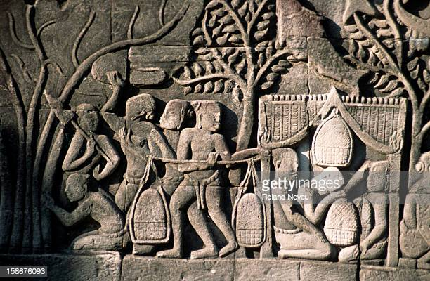 Bas relief at the Bayon temple in Angkor. This scene depicts a scene of market or donation..