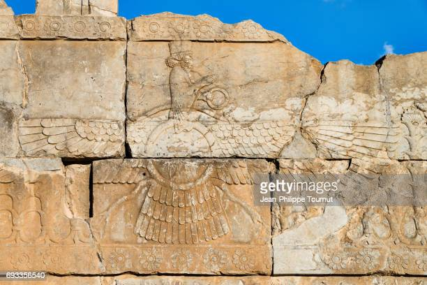 bas relief of faravahar (guardian spirit) in the ancient city of persepolis, shiraz, fars province, iran - mesopotamian art stock photos and pictures