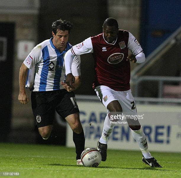 Bas Savage of Northampton Town attempts to move past Alan Lee of Huddersfield Town during the Johnstone's Paint Trophy 1st round match between...