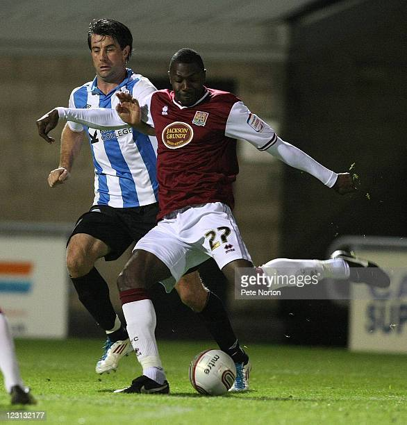 Bas Savage of Northampton Town looks to have a shot at goal watched by Alan Lee of Huddersfield Town during the Johnstone's Paint Trophy 1st round...