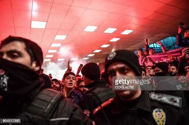 Basaksehir's supporters cheer and light flares as Barcelona's Turkish midfielder Arda Turan arrives at Ataturk International Airport in Istanbul on...
