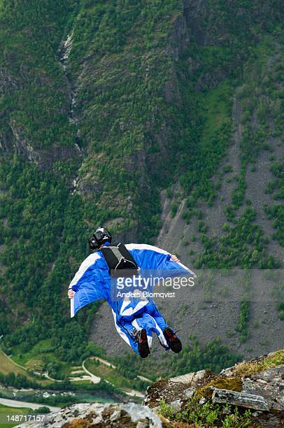 Base jumper in wingsuit  jumping off cliff high above Gudvangen near Voss.