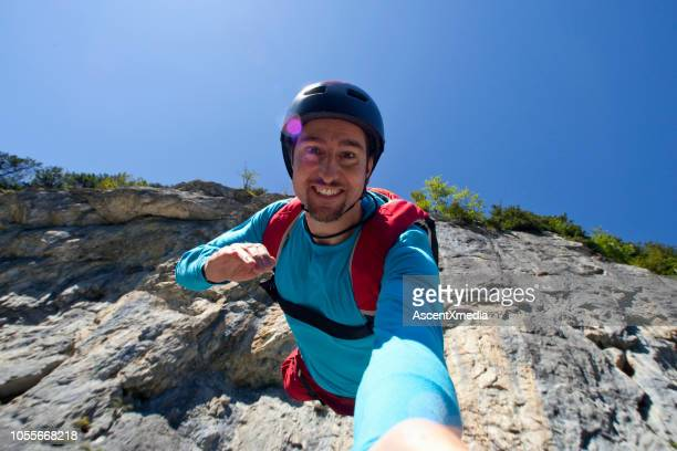 base jumper launches off cliff while smiling at camera - ascent xmedia stock pictures, royalty-free photos & images