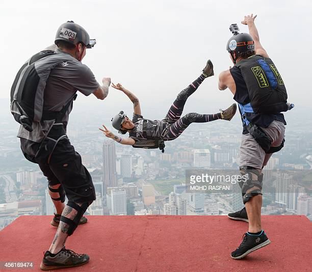 Base jumpers Alex Edge of the US and Jeff Weatherall of New Zealand throw Clair Marie of the US on her birthday from the 300metre high Open Deck of...