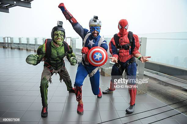 Base jumpers Cameron Minni of Canada Matthew Blanke of the US and Lawrence Jones of Australia pose for pictures clad in respective comic superhero...