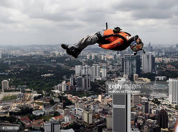 TOPSHOT Base jumpers leap from the 300metre high skydeck of Malaysia's landmark Kuala Lumpur Tower against the backdrop of the city's skyline on...