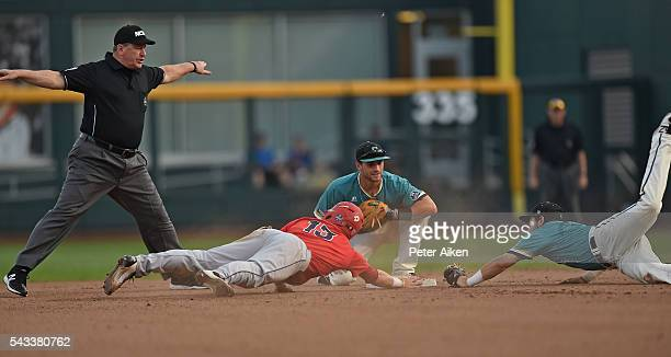 Base runner Cody Ramer of the Arizona Wildcats dives back to second safely against second basemen Tyler Chadwick and Michael Paez of the Coastal...