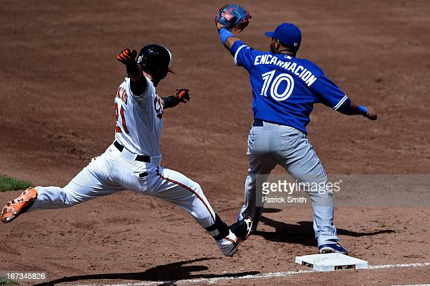 Base runner Nick Markakis of the Baltimore Orioles is forced out at first base as first baseman Edwin Encarnacion of the Toronto Blue Jays makes the...